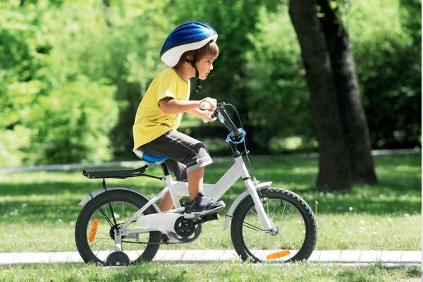 Мальчик 4 лет едет на детском велосипеде