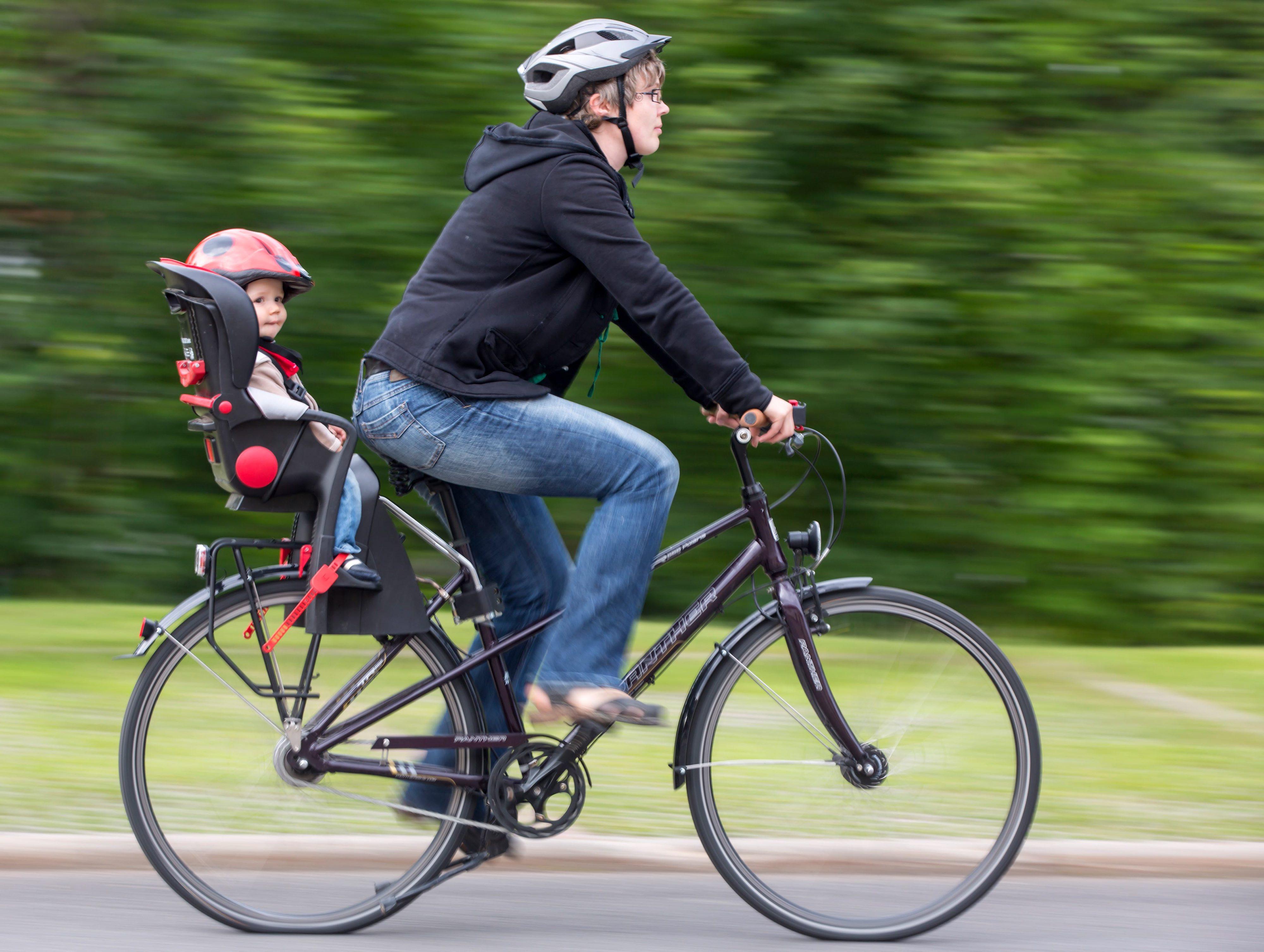 Женщина едет на велосипеде с ребенком на заднем кресле