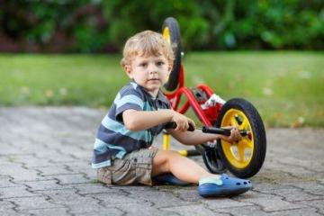 Маленький мальчик накачивает колесо своего детского велосипеда