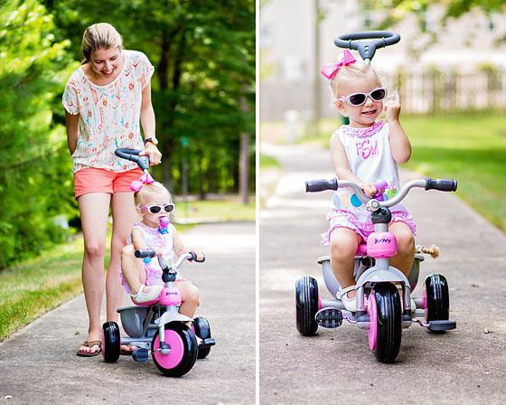 Ребнок на трехколесном велосипеде с ручкой в сопровеждении мамы