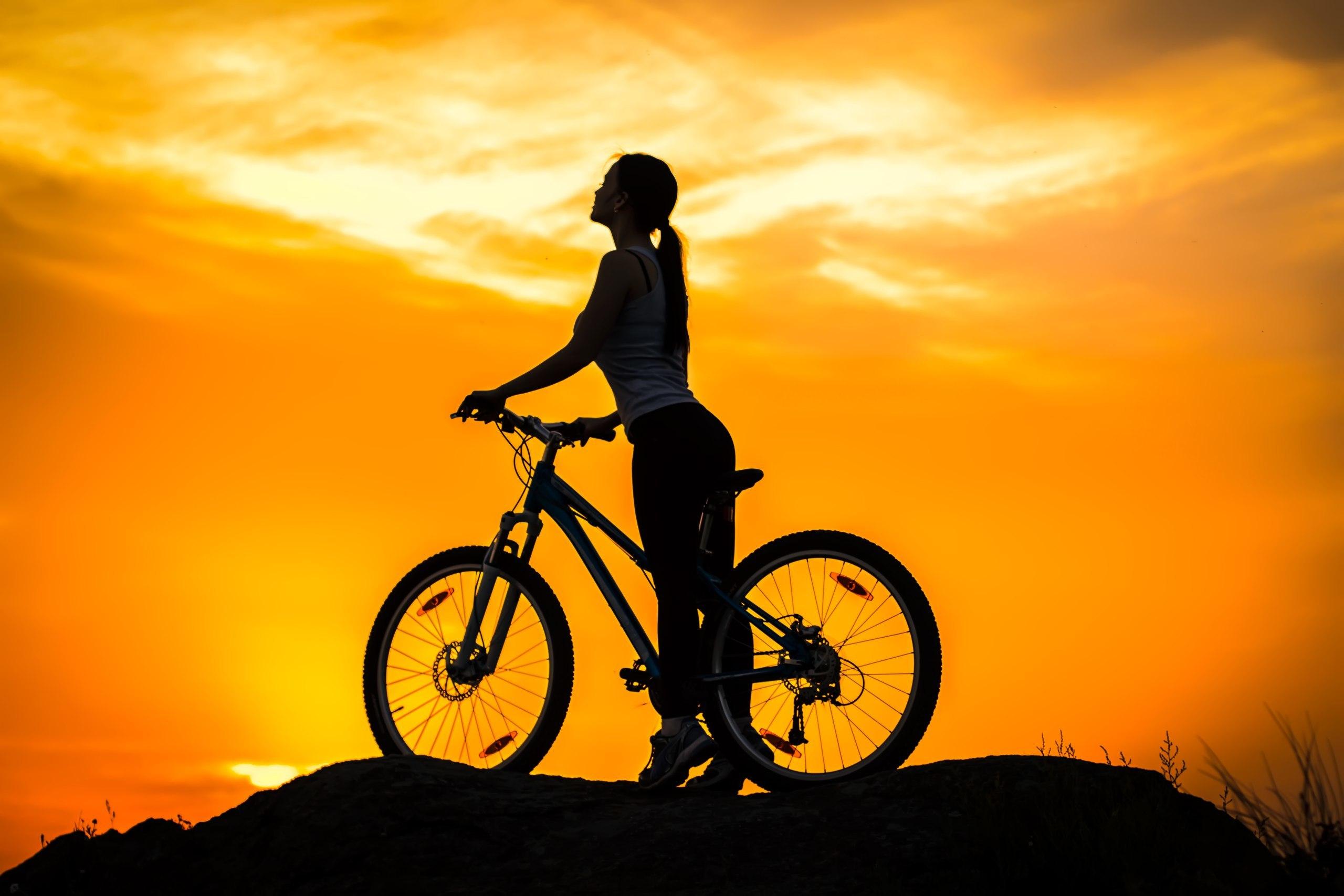 Девушка на закате с велосипедом