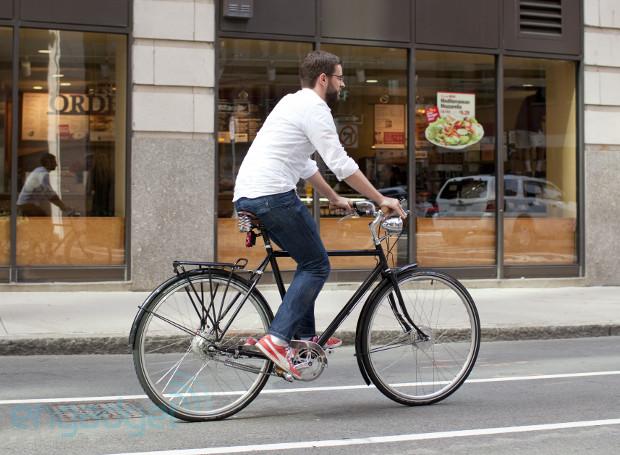 Мужчина едет по городу на городском велосипеде