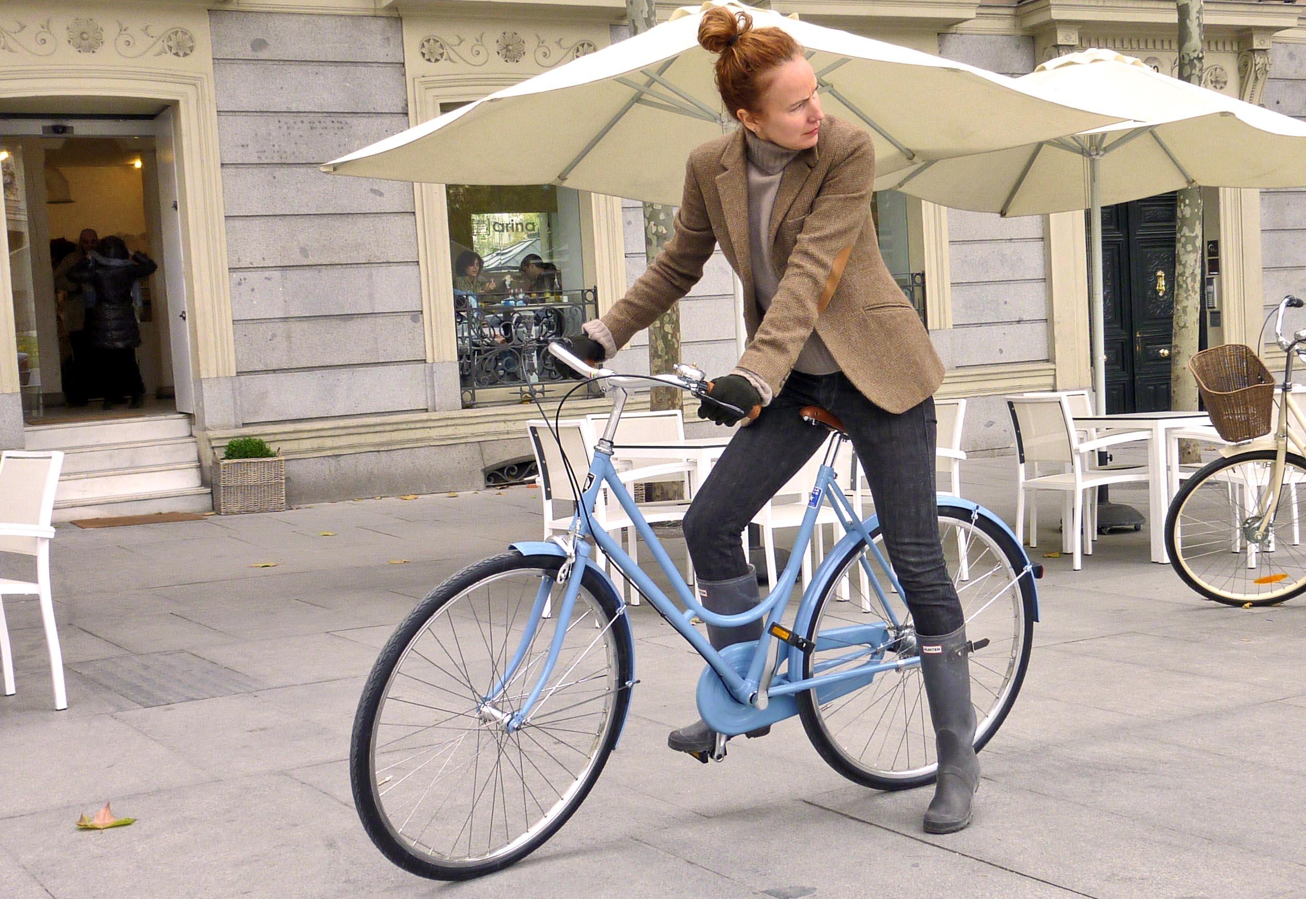 Женщина с городским велосипедом на улице города