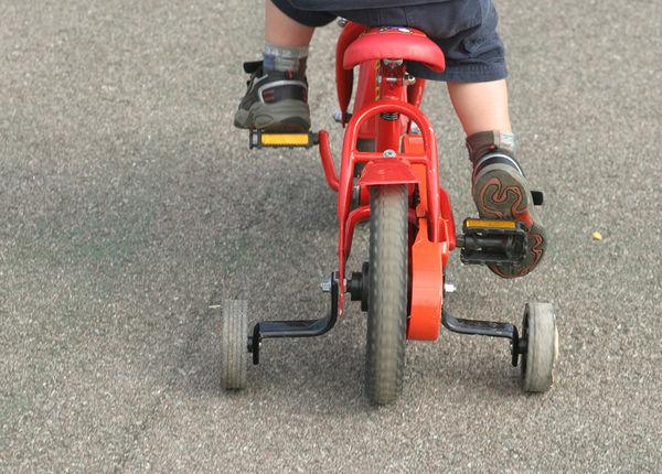 Вид сзади детского двухколесного велосипеда с боковыми колесами