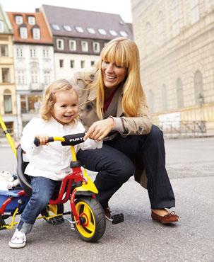 Женщина с ребенком на детском трехколесном велосипеде Puky