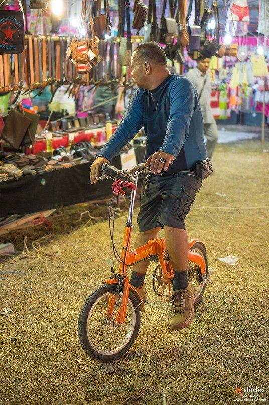 Мужчина едет на складном велосипеде