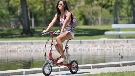 Девушка едет на складном велосипеде по парку
